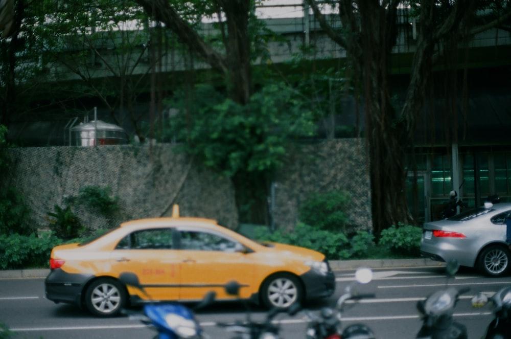 yellow and black sedan on road