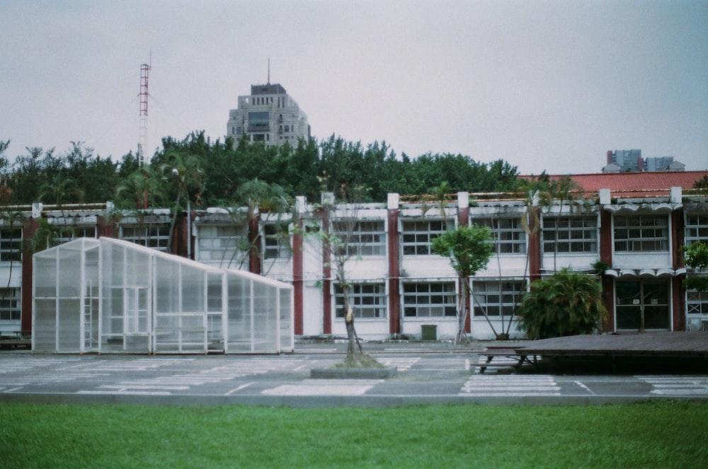 昼間の緑の芝生のフィールドの近くの白いコンクリートの建物