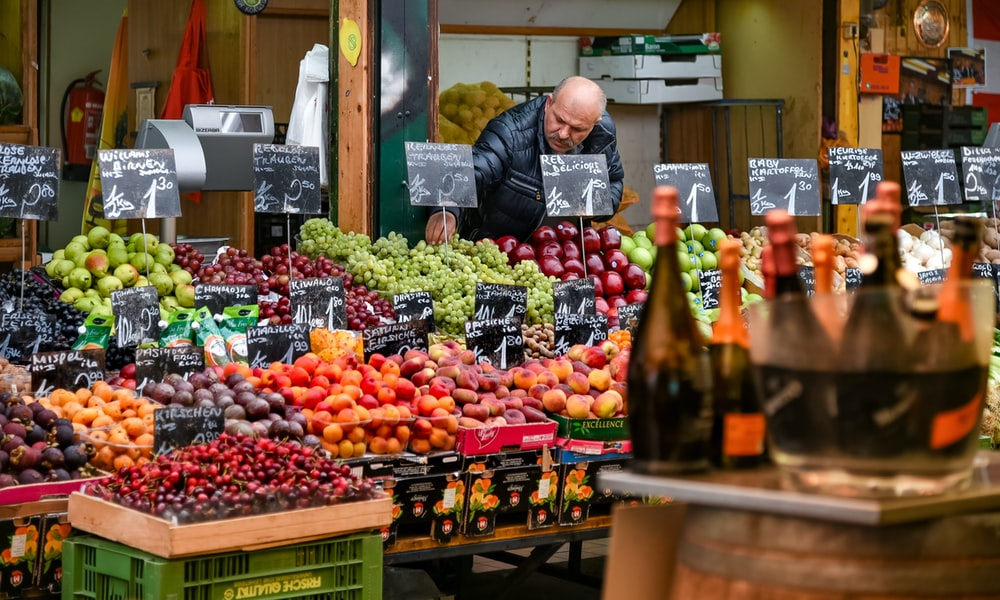 woman in black jacket standing in front of fruit stand