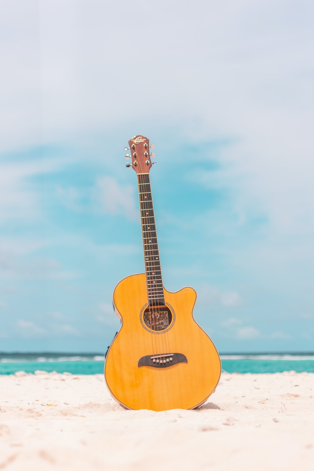 brown acoustic guitar on white sand during daytime