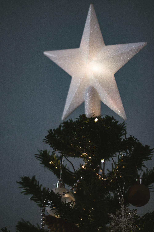 white star ornament on green christmas tree