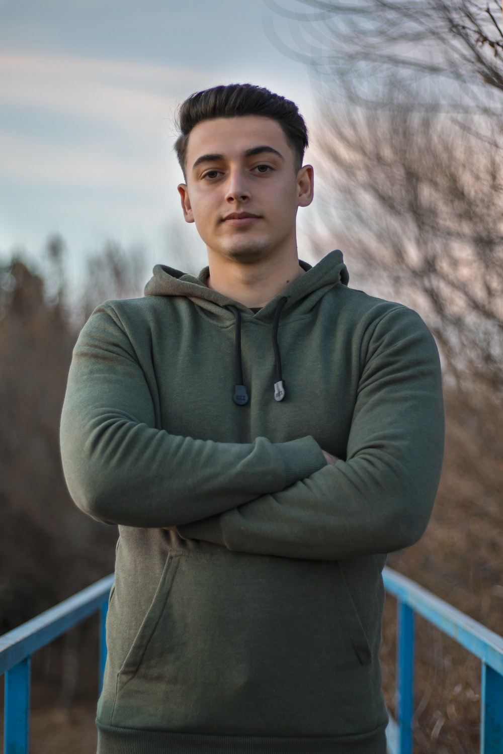 man in green hoodie standing on blue metal railings during daytime