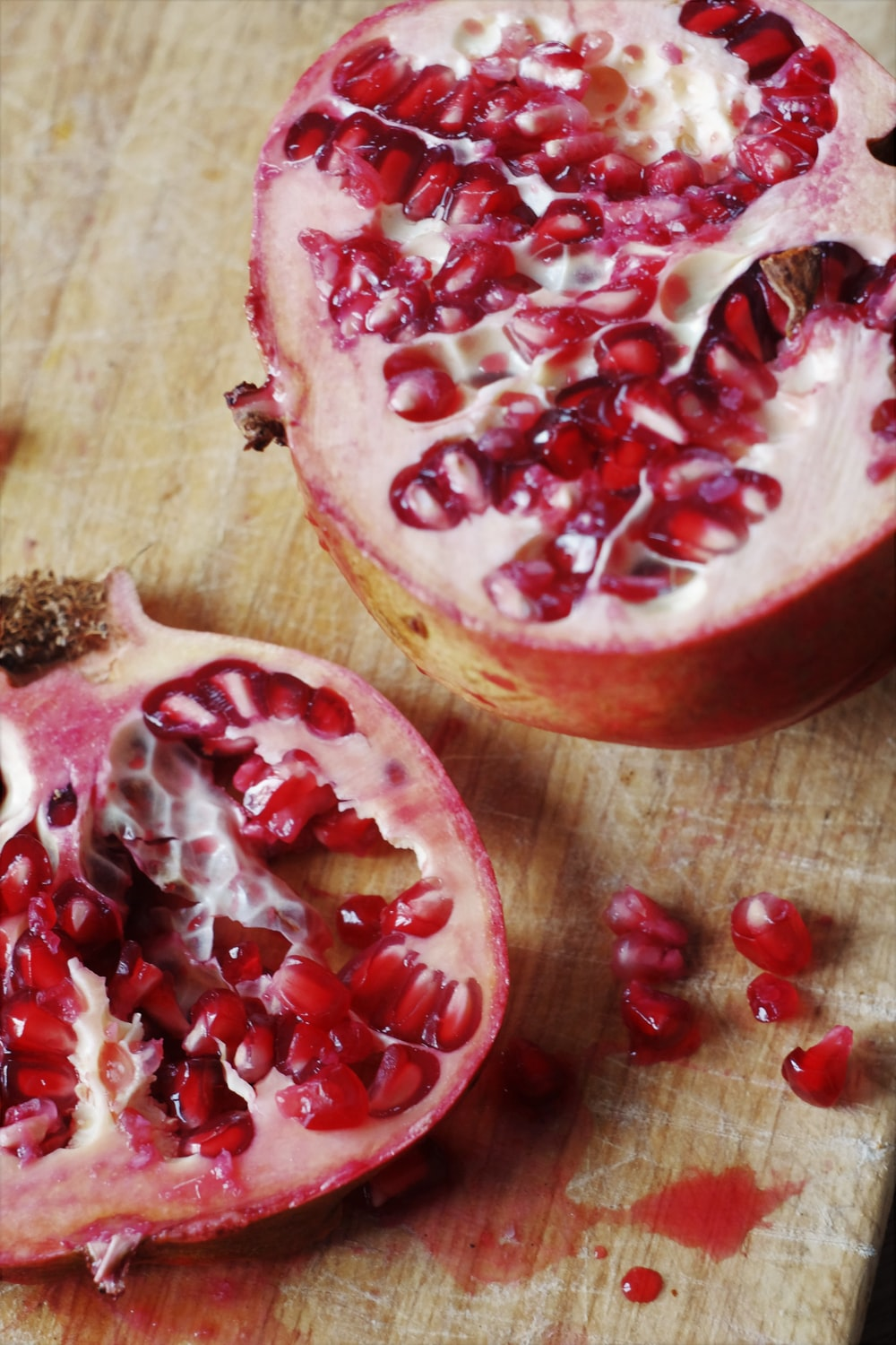 sliced pomegranate on brown wooden table