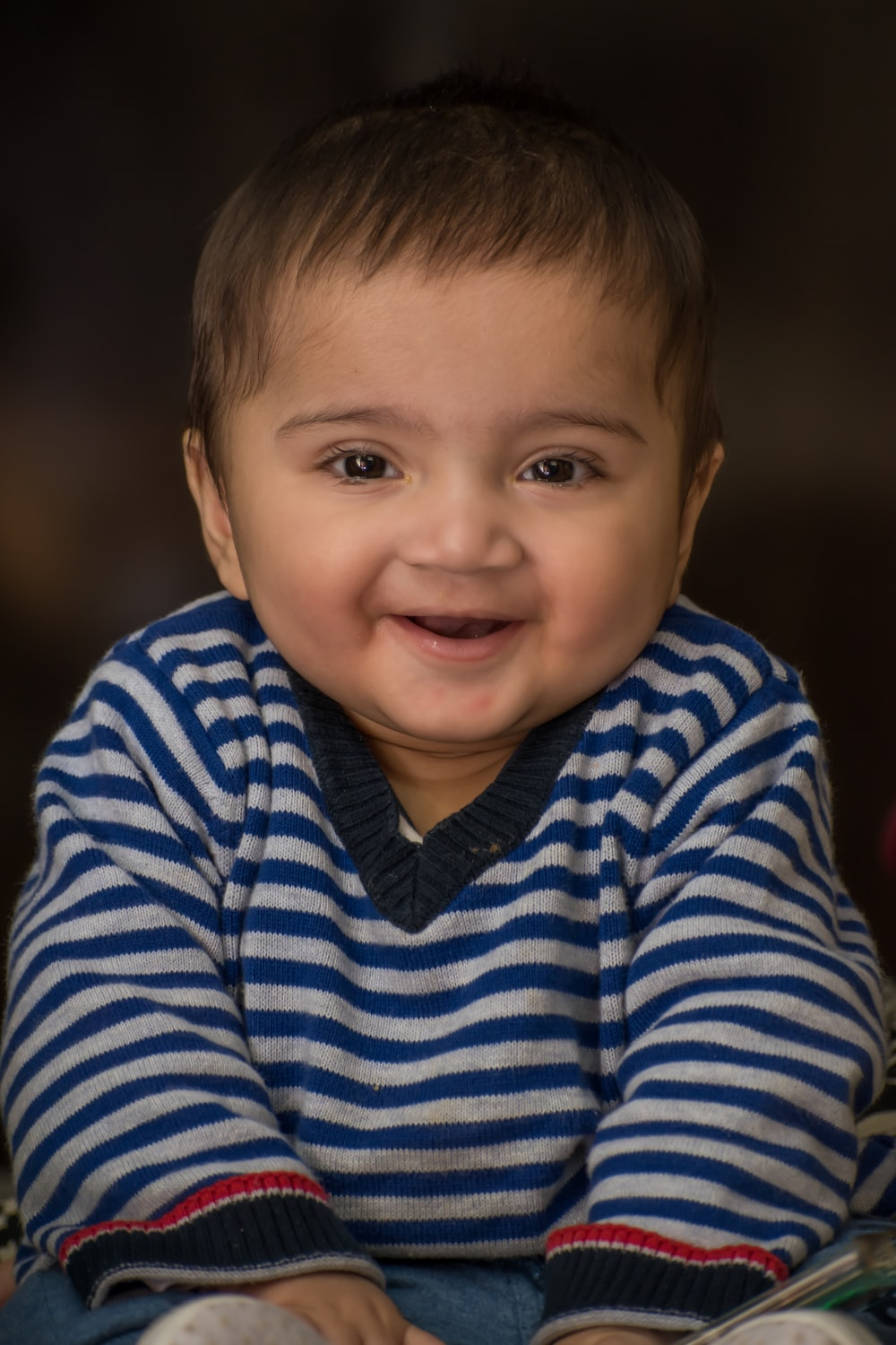 boy in blue and white striped long sleeve shirt smiling