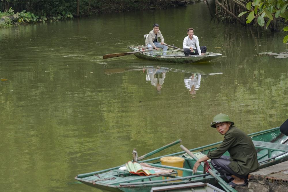 man in green shirt riding on white boat on lake during daytime