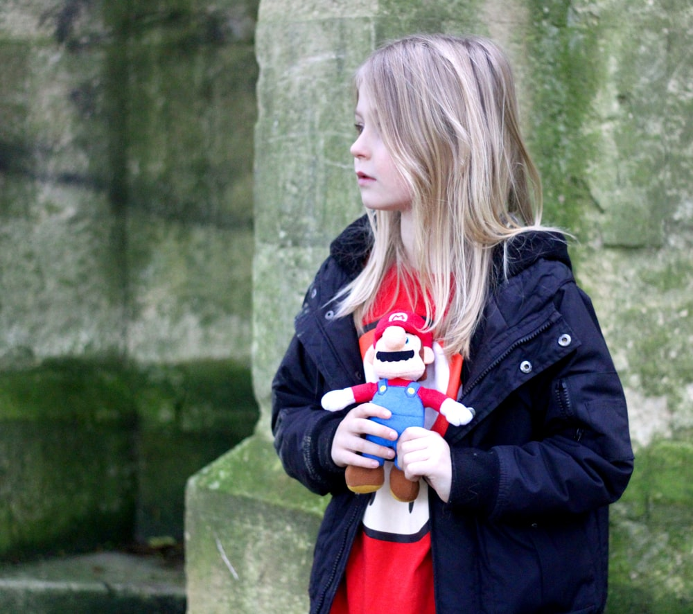 girl in black jacket holding red and white plush toy