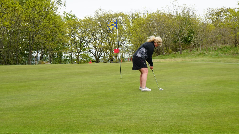 person in black jacket and white knit cap holding golf club