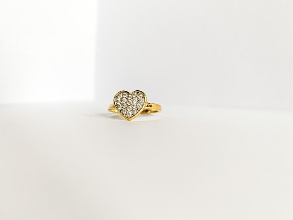 gold diamond ring on white surface