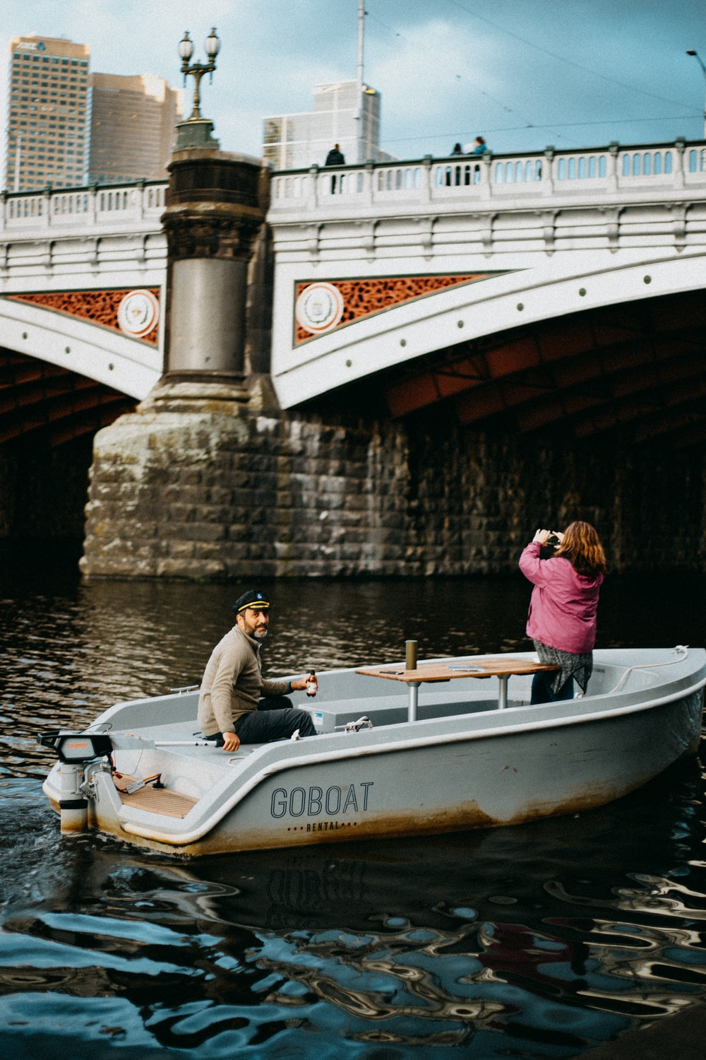 man and woman on white and blue boat on river during daytime