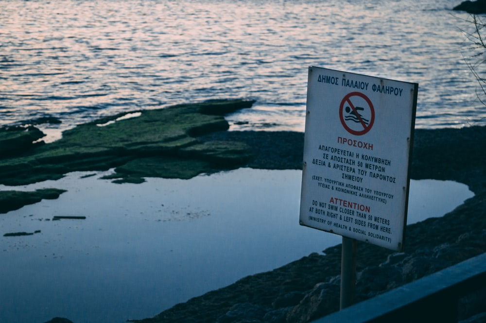 white and red labeled signage near body of water
