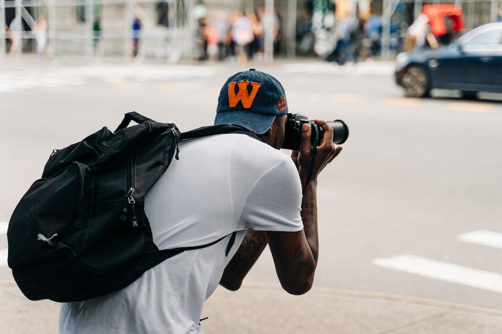 man in white shirt and black backpack taking photo using black dslr camera
