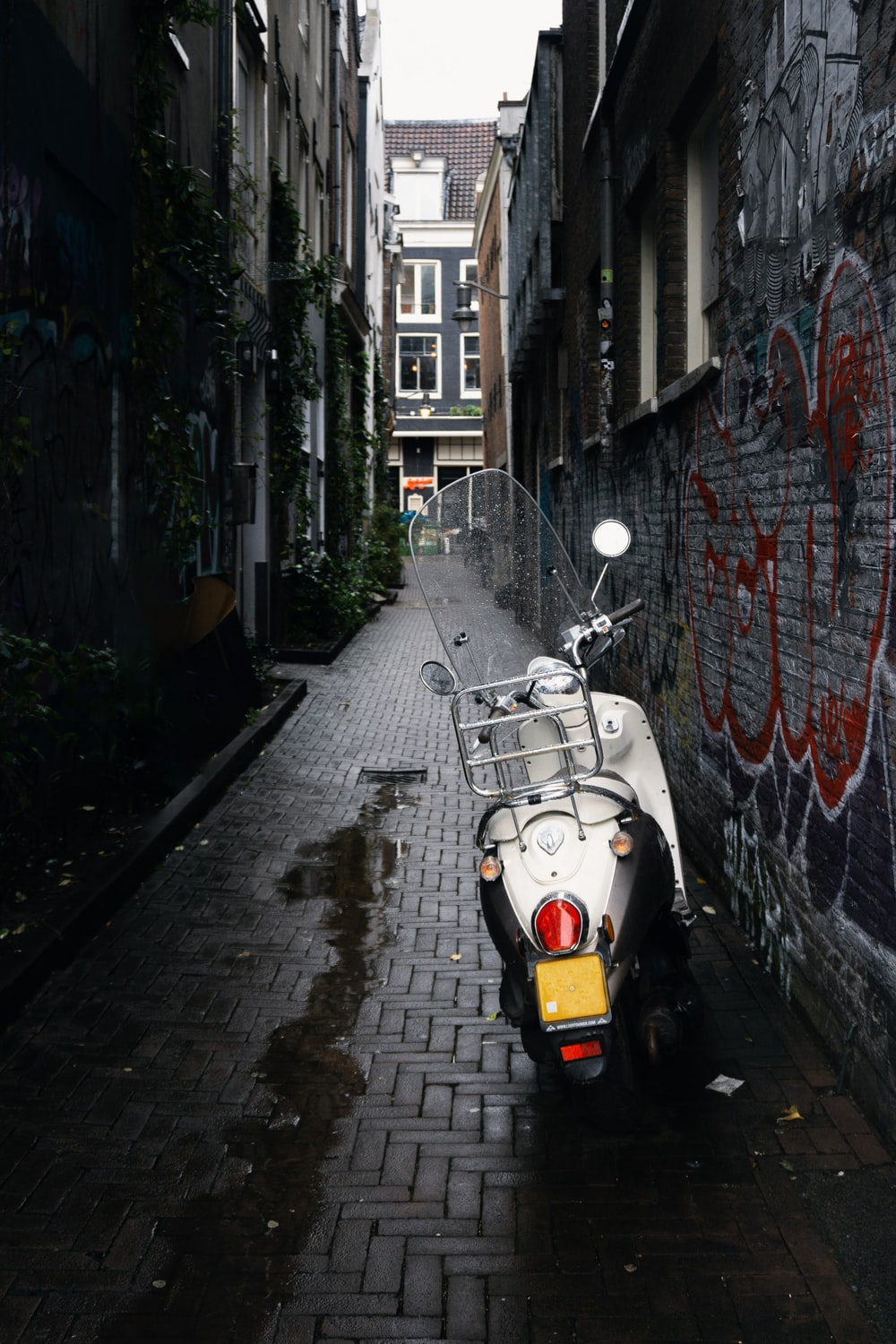 white motor scooter parked beside concrete building during daytime