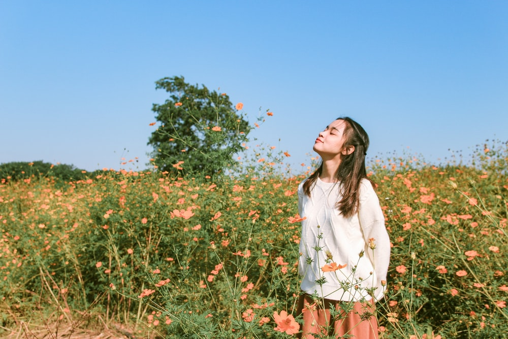 woman in white long sleeve shirt and brown skirt standing on flower field during daytime
