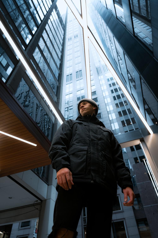 woman in black leather jacket standing near glass window