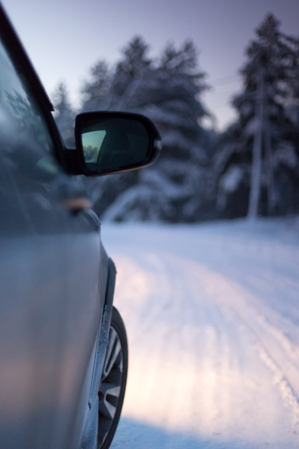 car side mirror with snow on the road