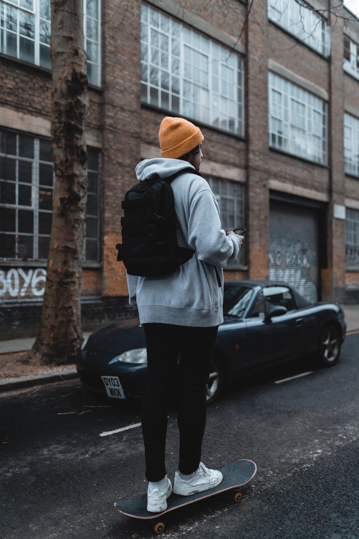woman in gray hoodie and black pants standing beside black car during daytime
