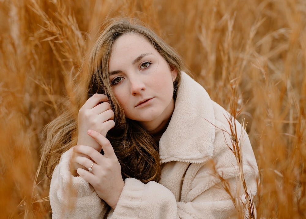 woman in white coat on brown grass field