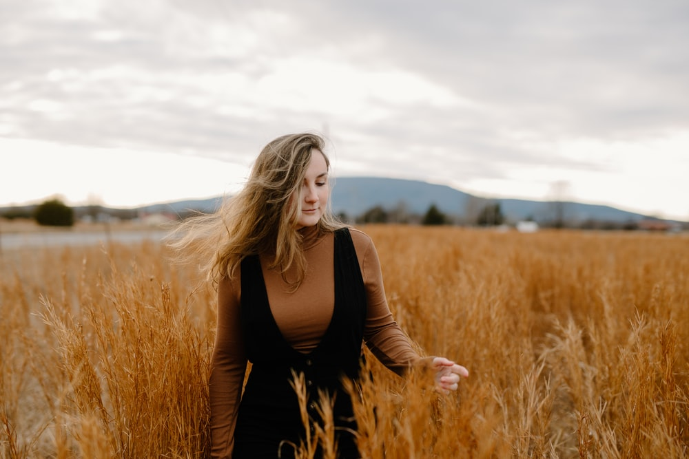 woman in black long sleeve shirt standing on brown grass field during daytime