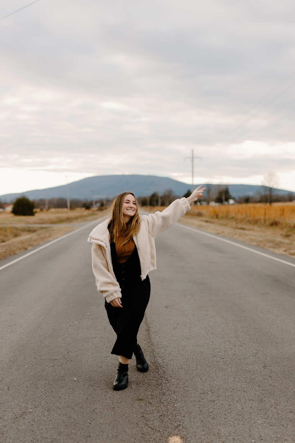 woman in white coat and black pants standing on road during daytime