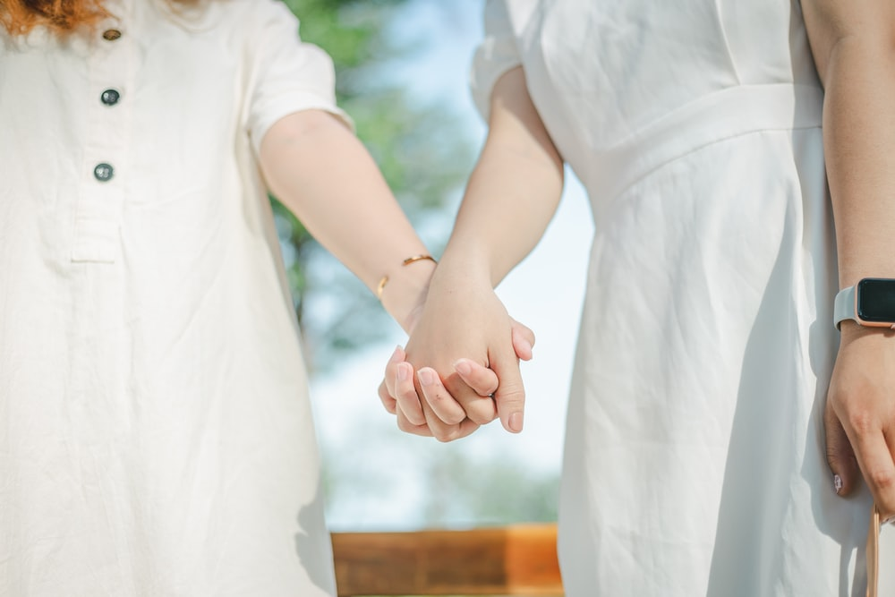 woman in white dress holding hands with girl in white dress