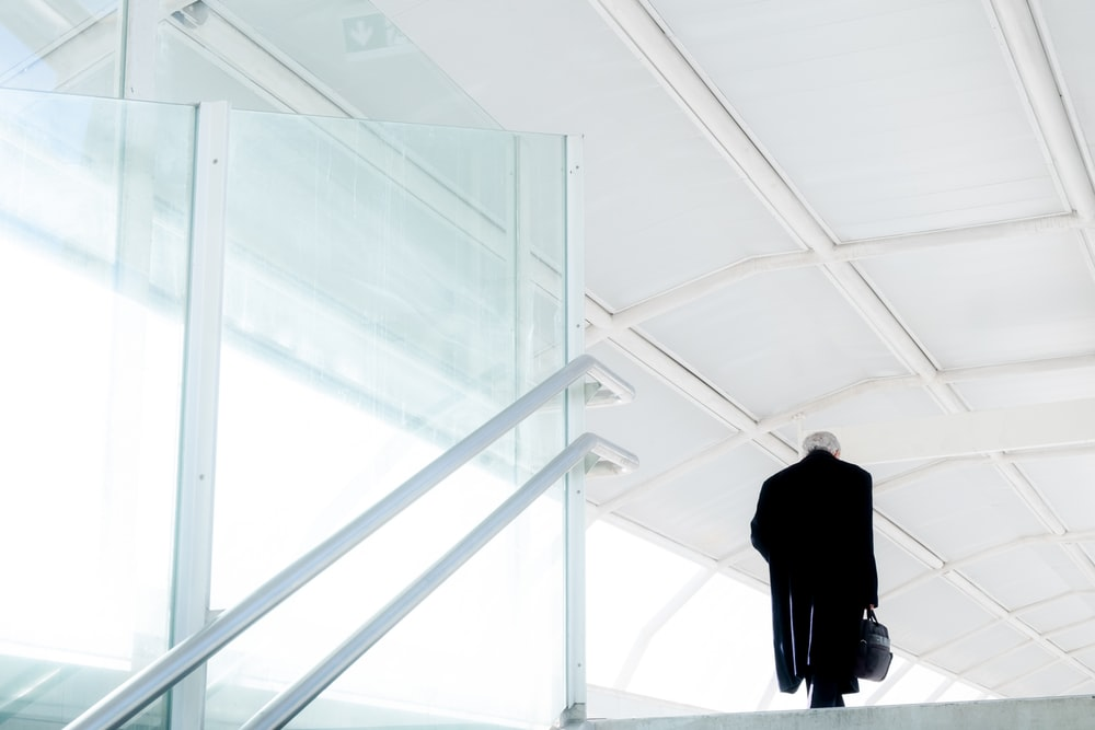 man in black suit standing on white staircase