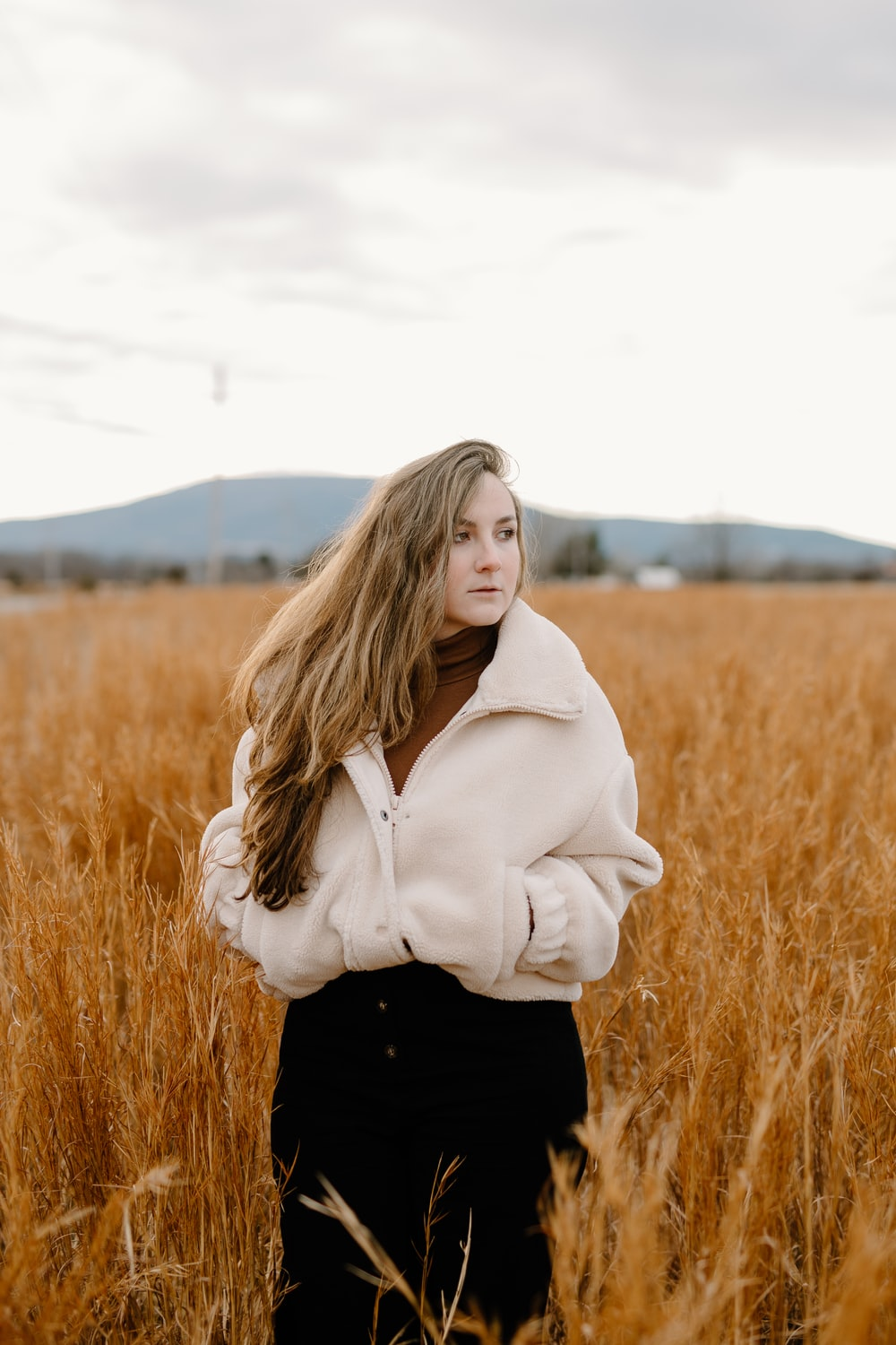 woman in white hoodie standing on brown grass field during daytime