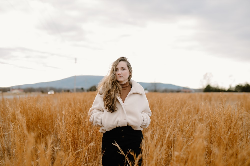 woman in white jacket standing on brown grass field during daytime