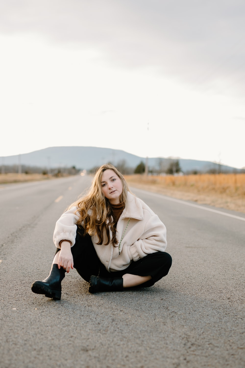 woman in white hoodie and black pants sitting on road during daytime