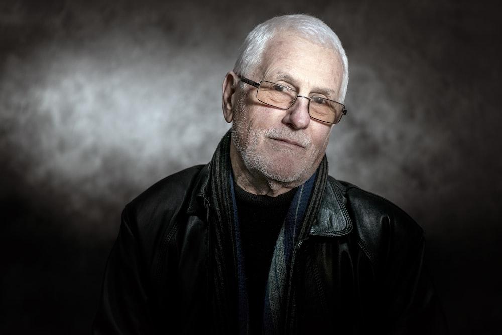 man in black leather jacket wearing eyeglasses