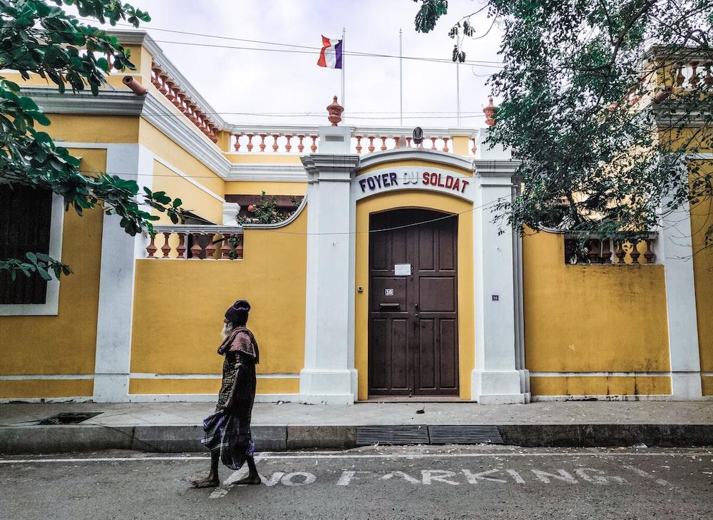 man in black jacket walking on sidewalk near yellow building during daytime