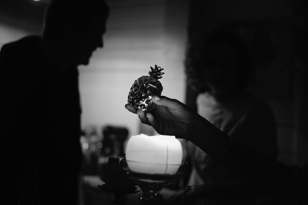 grayscale photo of person holding flower