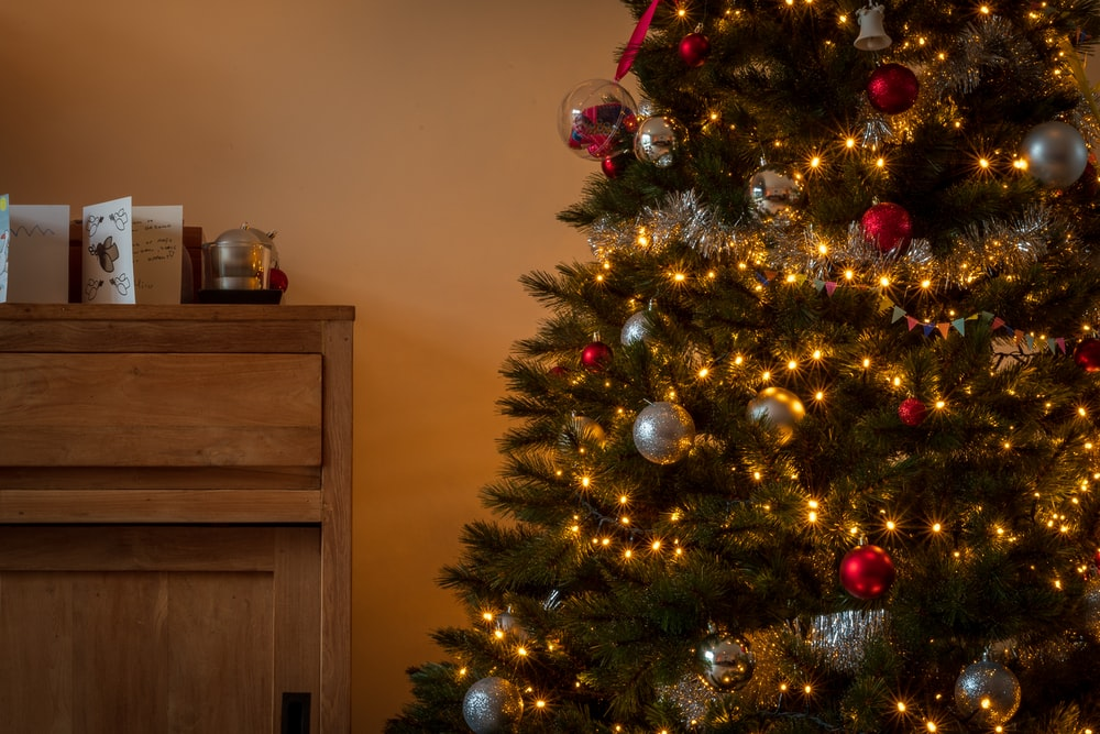 green christmas tree with red baubles and string lights