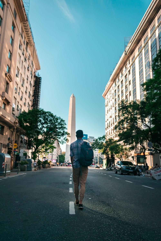 man in black jacket and brown pants standing on sidewalk during daytime