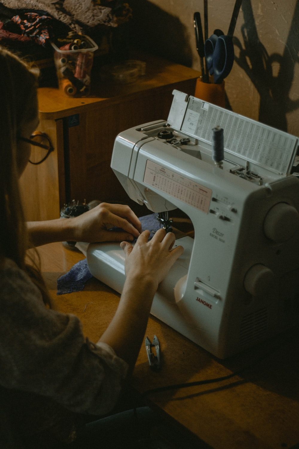 person using white sewing machine