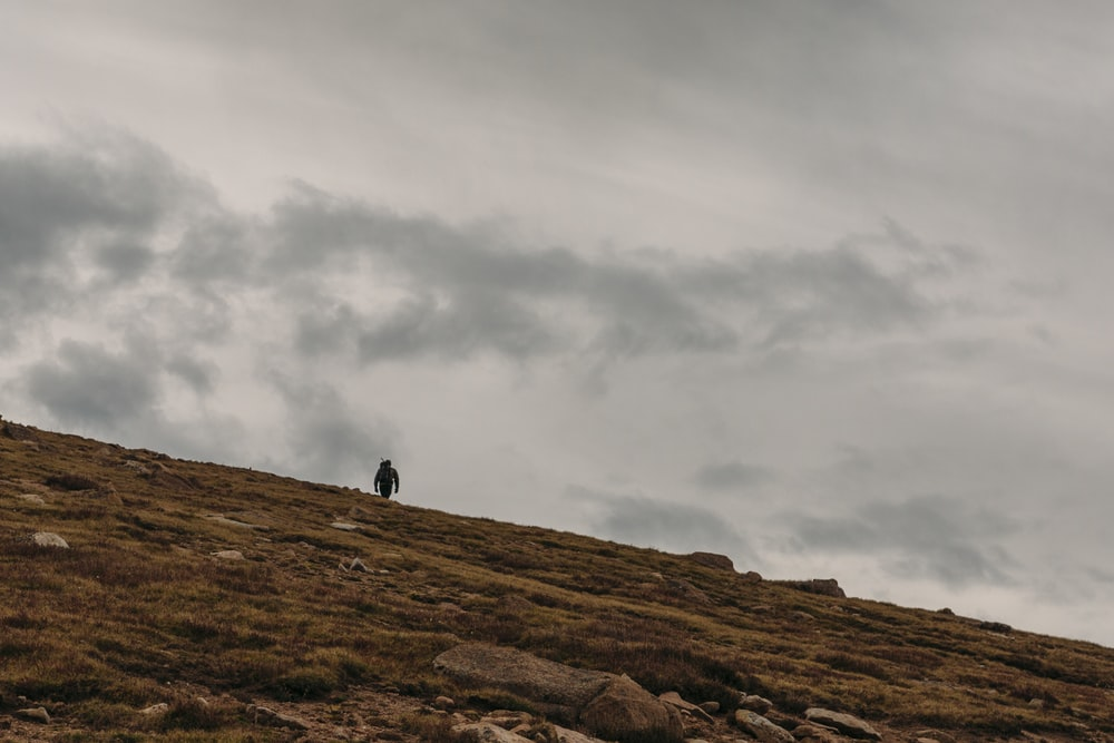 person standing on brown rock mountain under gray clouds during daytime