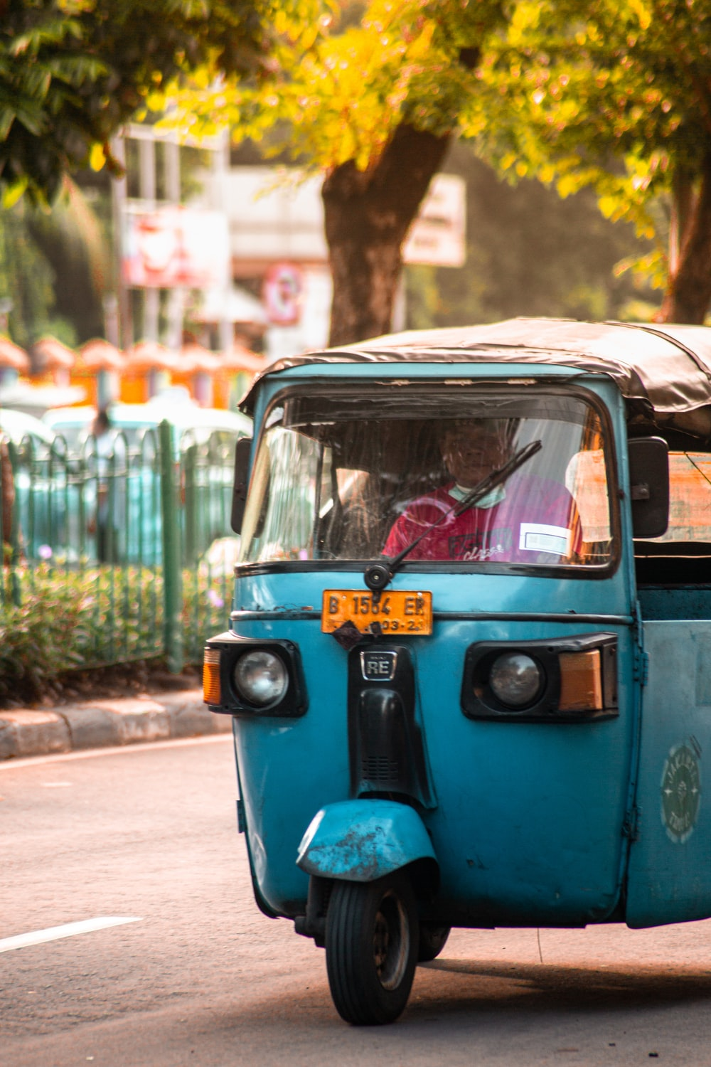 blue and black auto rickshaw on road during daytime