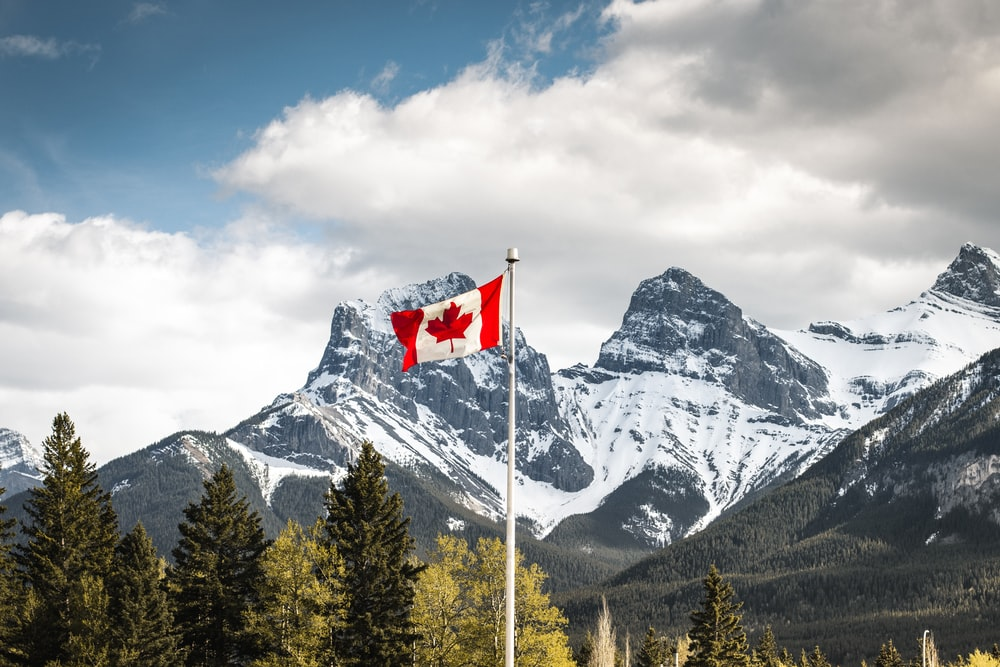 us a flag on pole near snow covered mountain