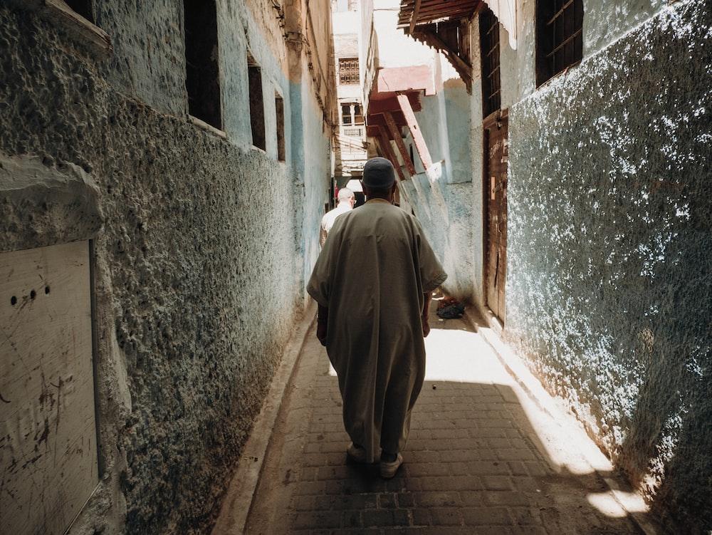 man in gray robe walking on street during daytime
