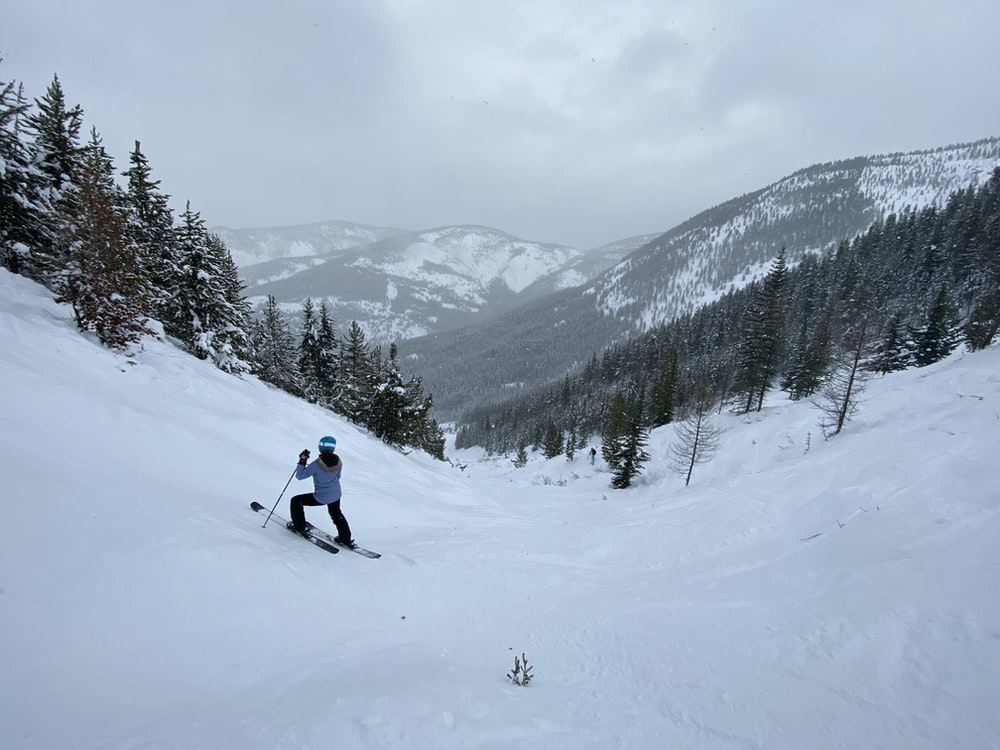 person in white jacket and black pants riding ski blades on snow covered mountain during daytime