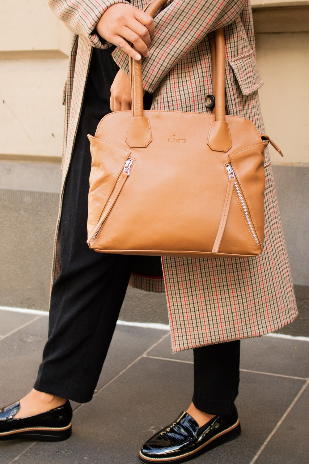 person in black pants holding brown leather handbag