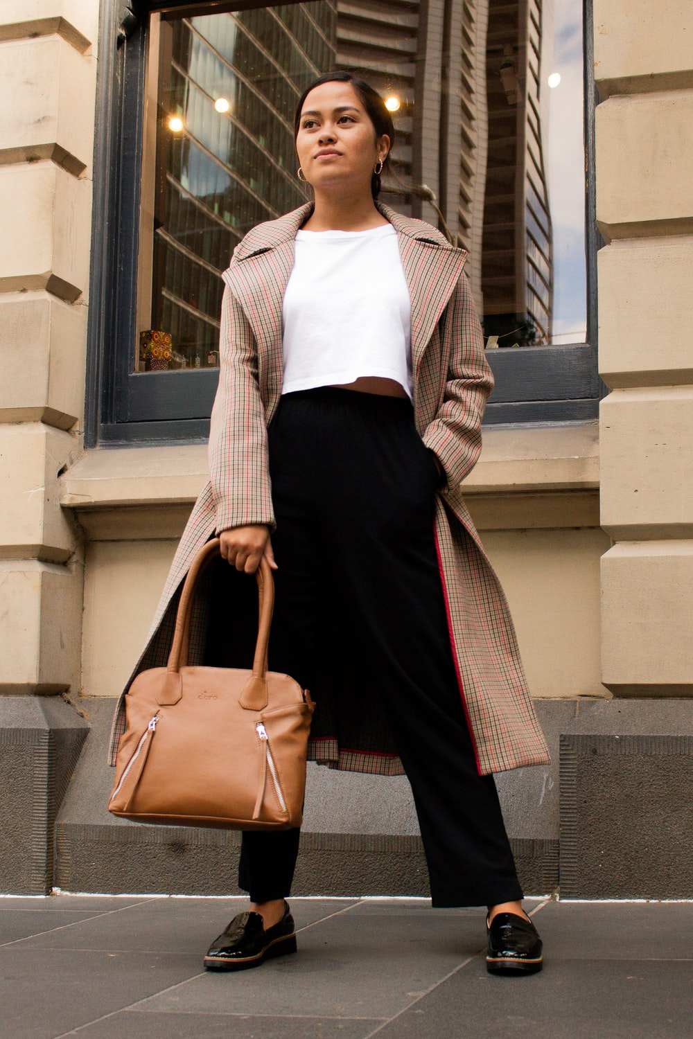 woman in white long sleeve shirt and black skirt holding brown leather handbag