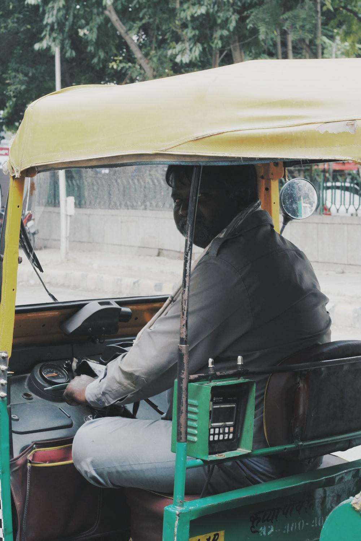 man in black jacket sitting on green and yellow auto rickshaw