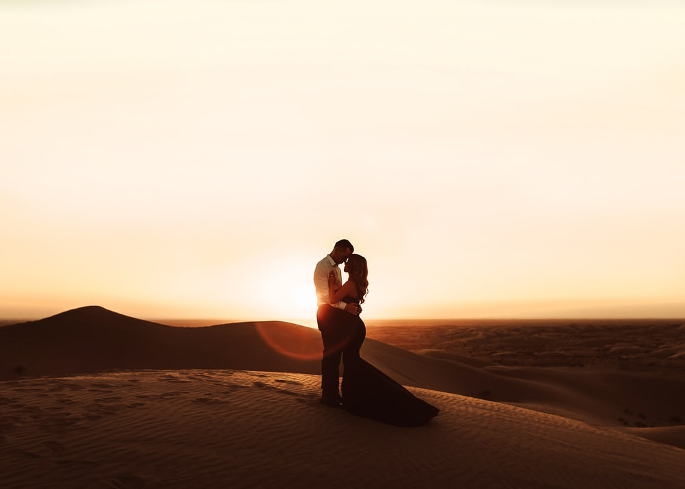 woman in black bikini standing on brown sand during sunset