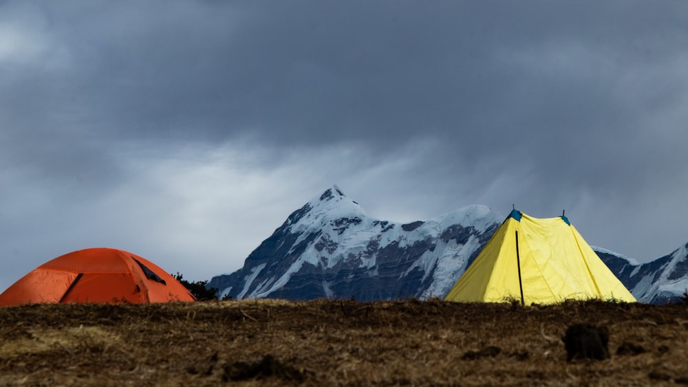 orange tent on brown grass field near snow covered mountain during daytime