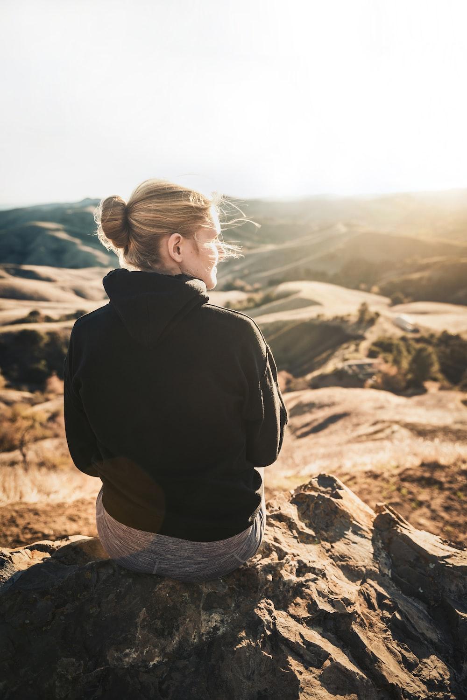 man in black hoodie and gray denim shorts sitting on brown rock during daytime