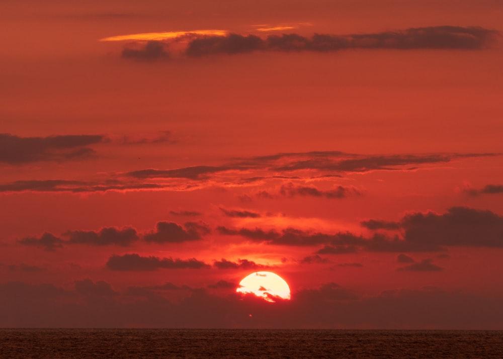 body of water under orange sky during sunset