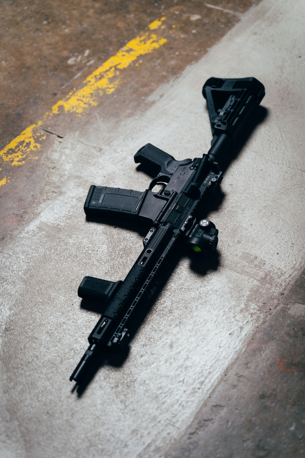black rifle on brown wooden table