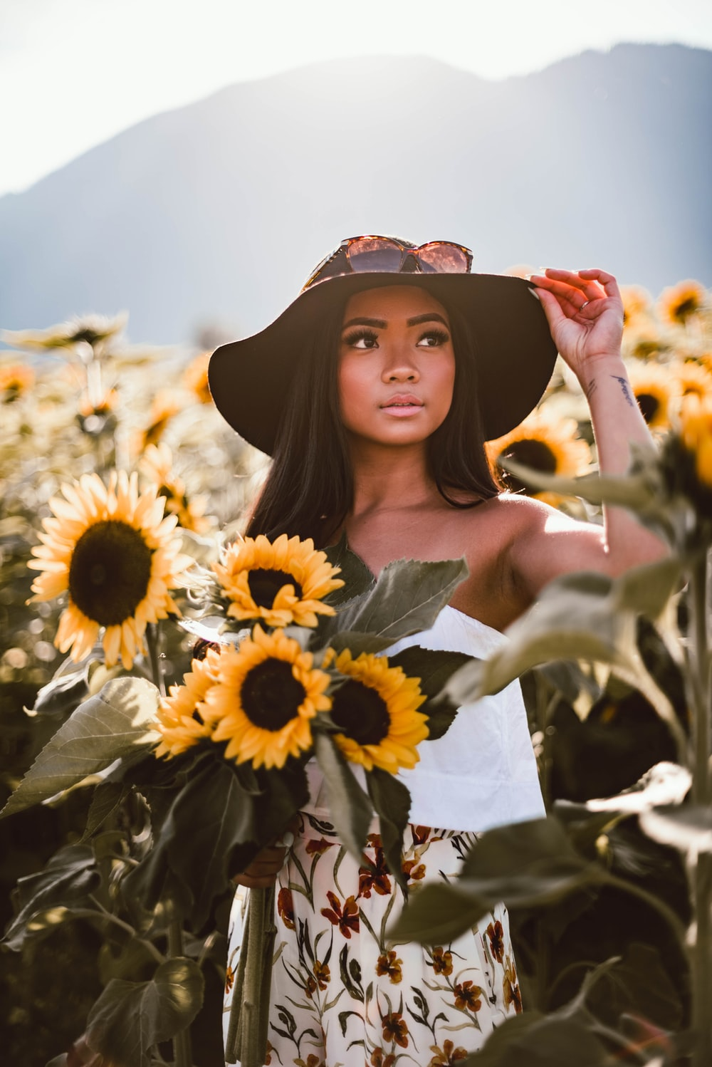 woman in black off shoulder dress standing on sunflower field during daytime