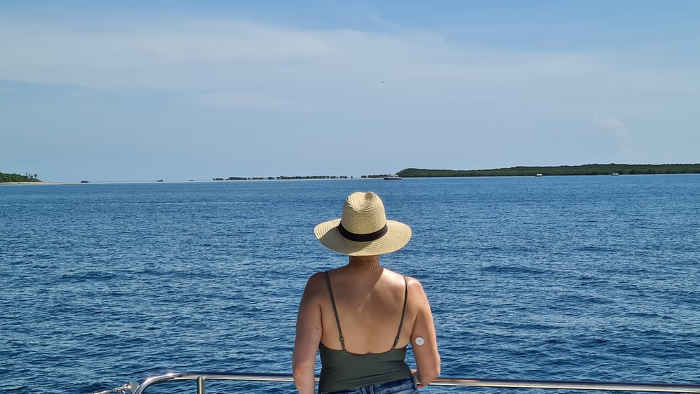 woman in brown sun hat and brown tank top sitting on boat during daytime