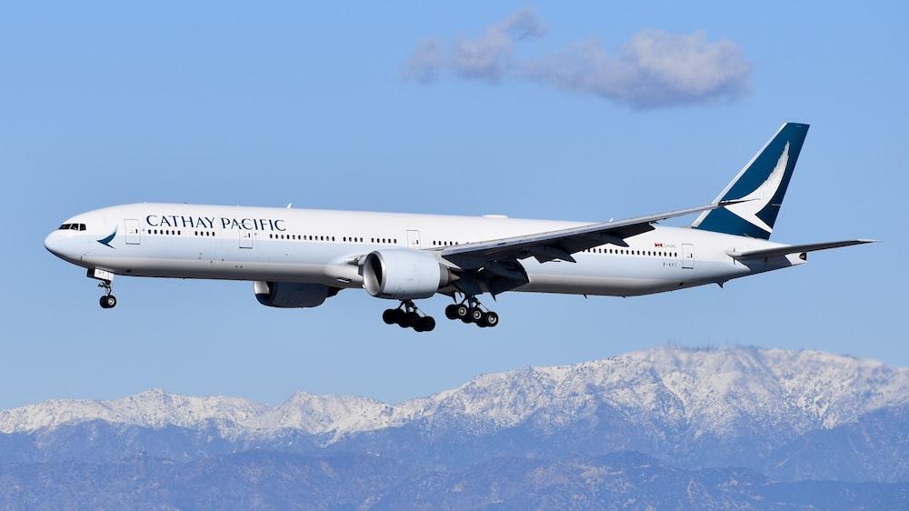 white passenger plane flying over snow covered mountain during daytime